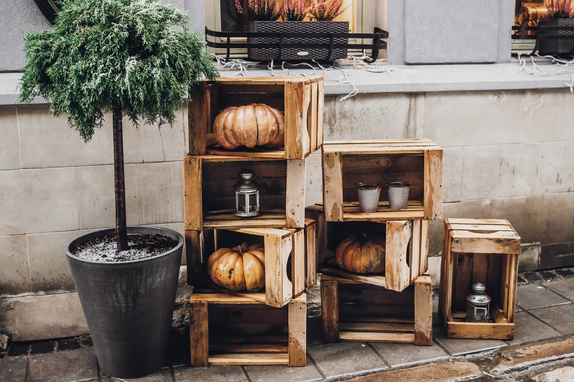 rustic decoration with pumpkins and lanterns in wooden boxes